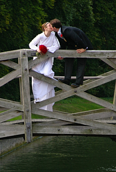 Wedding bride and groom kissing on bridge