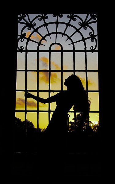 Silhouette of woman at sunset against railings