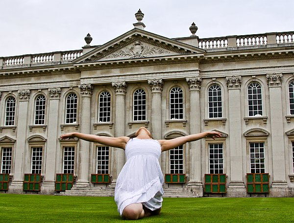 Dancer in white, in front of building