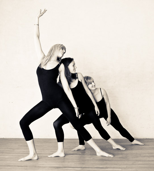 Three dancers posing together in a curve