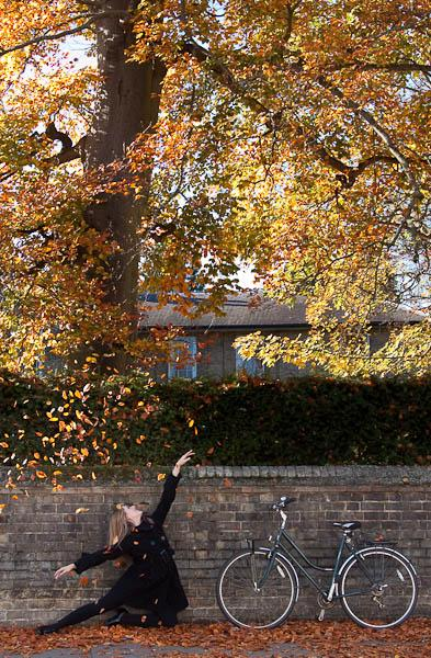 Ballet Dancer in autumn leaves with bike